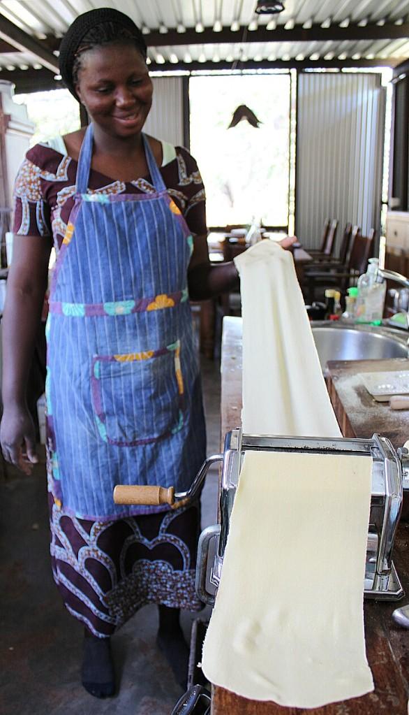 Adelina pressing the dough through the pasta-making machine.