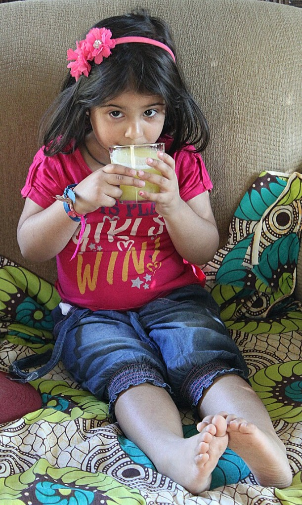 A little person enjoying the fresh pineapple juice.