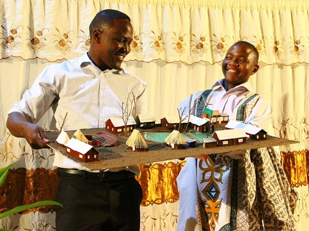 A Tujatane student presents Deputy Sydney, the Performing Arts guru, with a model of the school he crafted as a thank you gift.