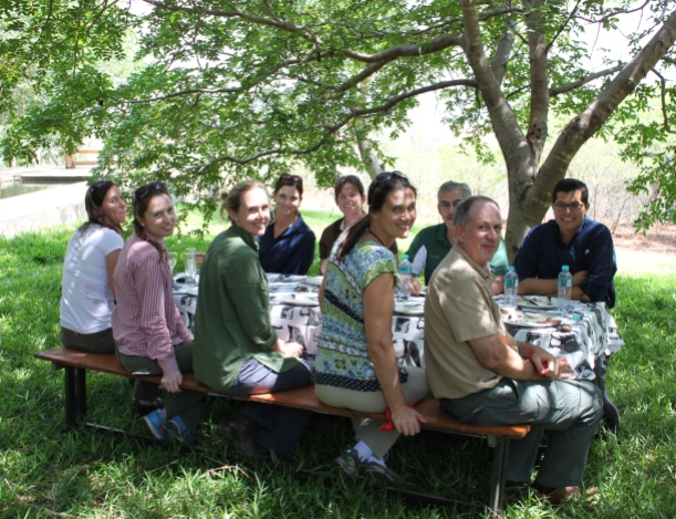 A table of agricultural leaders from California enjoying lunch under the teak trees.