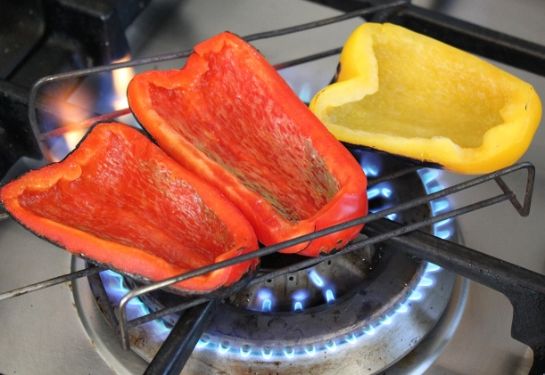 Blackening skins of the peppers over the direct flame of the gas hob.